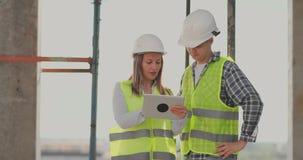 Het bouwwerfteam of de architect en de bouwer of de arbeider met helmen bespreekt op een plan van de steigerbouw of stock video