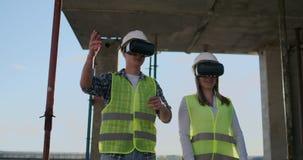 Het bouwwerfteam of de architect en de bouwer of de arbeider met helmen bespreekt op een plan van de steigerbouw of stock videobeelden