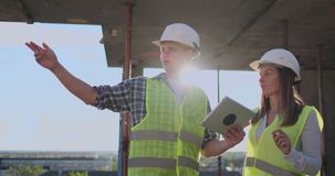 Het bouwwerfteam of de architect en de bouwer of de arbeider met helmen bespreekt op een plan van de steigerbouw of stock footage