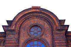 Het bovenste gedeelte van het uitstekende gebouw Een muur van donkerrode baksteen Uitstekend rond venster Royalty-vrije Stock Fotografie