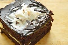 Het bovenste laagje die van de chocoladecake witte chocolade op houten karbonadeblok snijden Stock Afbeeldingen