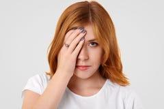 Het boze droevige wijfje behandelt de helft van gezicht na ruzie met vriend, die in lage geest zijn, heeft freckled huid, kijkt m stock afbeeldingen