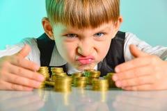 Het boze en gulzige kind houdt hun geldmuntstukken Het concept hebzucht, hebzucht en ondeugd van kinderjaren stock afbeeldingen