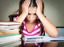 Het boze en vermoeide schoolmeisje bestuderen Stock Afbeeldingen