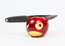 Het boze gezicht is gesneden op een appel en een mes Stock Foto