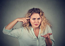 Het boze vrouw gesturing tegen tempel is gek u? stock foto