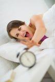 Het boze vrouw uitrekken zich om wekker uit te zetten Royalty-vrije Stock Foto