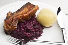 Het braadstuk van de varkensvleesbuik met zuurkool en bollen Stock Foto's
