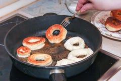 Het braden donuts in pan stock foto's