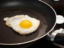 Het braden van een ei Stock Afbeeldingen