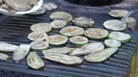 Het braden van verse gesneden courgette en aubergine op net