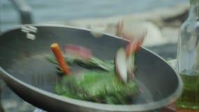Het braden van verse groenten in een pan op Open Vlam stock videobeelden