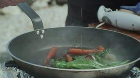 Het braden van verse groenten in een pan op Open Vlam stock video