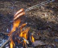 Het branden van de hotdogs over een brand Royalty-vrije Stock Fotografie