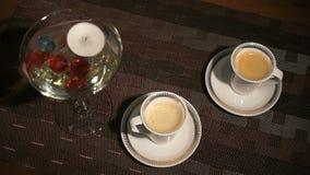 Het branden van de kaars verspreide halfedelstenen Twee koppen van mooie aromatische koffie stock video