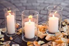 Het branden van kaarsen in een vaas met roze-doorbladert stock foto's