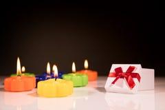 Het branden van kleurrijke kaarsen met gift Stock Foto