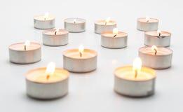 Het branden van paraffinekaarsen, tealight, ligt op een witte achtergrond royalty-vrije stock foto's