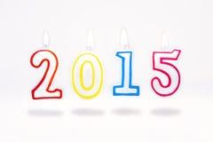 Het branden van rode kaarsen die met nummer 2015 op witte achtergrond vliegen Stock Fotografie