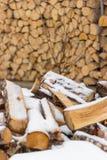 Het brandhout ligt onder de sneeuw tegen de achtergrond van het gevouwen brandhouthuis Brandhout voor de open haard en het fornui stock afbeelding