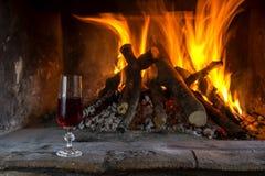 Het brandhout in open haard branden en een glas die wijn stock afbeeldingen
