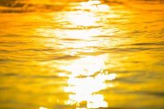 het brandingsoverzees blured golf bij de gouden lichte achtergrond DE van het zonsondergangstrand Stock Foto