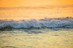 het brandingsoverzees blured golf bij de gouden lichte achtergrond DE van het zonsondergangstrand Stock Afbeeldingen
