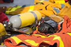 Het brandweermanzuurstofmasker en de luchttank met materiaal treffen voor oper voorbereidingen Stock Foto