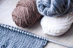 Het breien met grijze wol en bruine grijze en witte wol Stock Foto