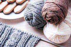 Het breien met grijze wol en bruine grijze en witte wol Stock Foto's