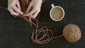 Het breien van een sok met koffie stock videobeelden