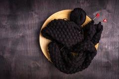 het breien van zwarte draden in een plaat op een zwarte en grijze houten achtergrond royalty-vrije stock foto
