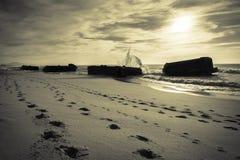 Het breken van bespattende golf op oud oorlogsblokhuis op toneel mooi zandig strandzeegezicht met golven Royalty-vrije Stock Afbeeldingen