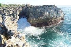 Het breken van blauwe golven op een rots op een zonnige dag Royalty-vrije Stock Fotografie