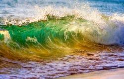 Het breken van oceaangolf bij zonsondergang Stock Foto's