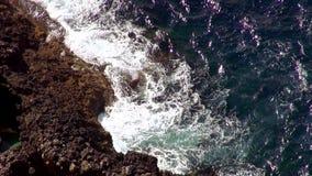 Het breken van oceaangolven bij het klippen luchtschot stock videobeelden