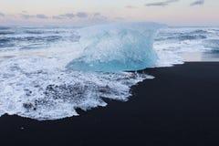 Het brekende Ijs van IJsland op het zwarte strand van het lavazand Stock Afbeeldingen