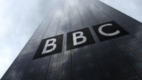 Het Britse embleem van het Omroepbbc op een wolkenkrabbervoorgevel die op wolken wijzen Het redactie 3D teruggeven Stock Foto's