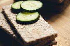Het brood maakte van rogge en tarwemeel met vers gesneden en groene stukken van komkommer, ligt op een raad voor scherp voedsel V Royalty-vrije Stock Afbeeldingen