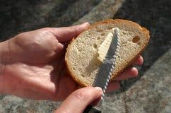 Het brood van Buttering Stock Afbeeldingen