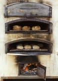 Het brood van het baksel in traditionele houten oven Royalty-vrije Stock Foto's