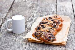 Het broodje van het papaverzaad op de lijst met witte mok van de melk vers wordt gebakken die Stock Afbeelding