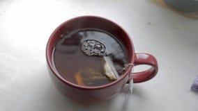 Het brouwen in een rode koraalkop van een theezakje Overstromende thee met kokend water van de ketel stock video