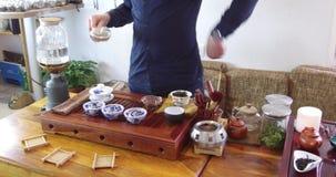 Het brouwen van Chinese thee in ceramische gaiwan tijdens het close-up van de theeceremonie Gaiwan en andere theehulpmiddelen voo