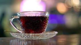 Het brouwen van zwarte thee met warm water in een glaskop stock footage