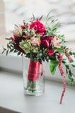 Het bruidboeket van huwelijk bloeit rode en beige pioenen, lelie, groen in vaas op witte achtergrond kleurenmarsala Stock Afbeeldingen