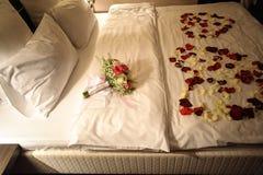 Het bruids boeket en nam bloemblaadjes op het bed met witte linens toe stock afbeeldingen