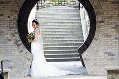 Het bruids boeket van de bruidgreep met witte huwelijkskleding dichtbij een baksteenboog Royalty-vrije Stock Foto