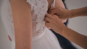 Het bruidsmeisje helpt bruid om huwelijkskleding te dragen Mening van bovenkant stock video