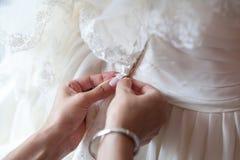 Het bruidsmeisje helpt de bruid zich te kleden Stock Foto